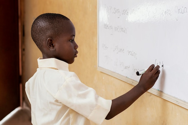Afrikanisches kind, das auf einem whiteboard schreibt