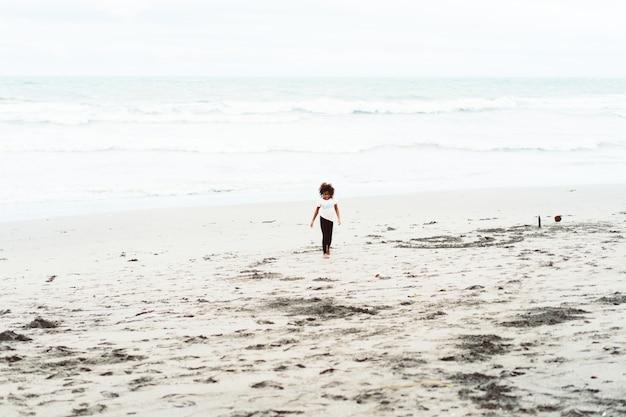 Afrikanisches mädchen, das spaß am sandigen strand hat