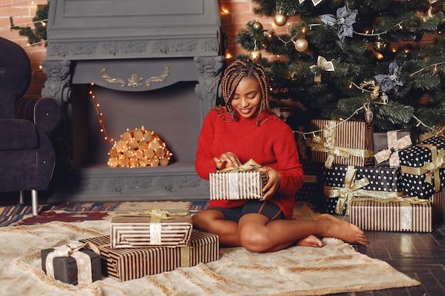 Afrikanisches mädchen in einer weihnachtsdekoration / frau in einem roten pullover. neujahrskonzept.