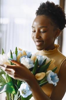 Afrikanisches mädchen mit blüte. strauß tulpen in händen. frau am fenster.