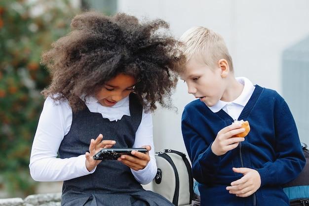 Afrikanisches mädchen und ein blonder junge sitzen auf den stufen und spielen am smartphone.