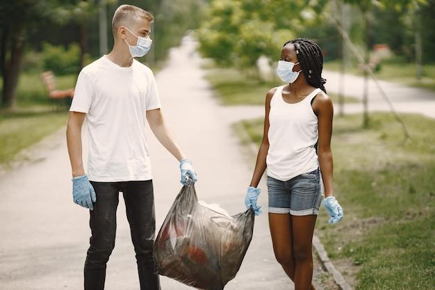 Afrikanisches mädchen und europäischer junge mit masken und handschuhen. sie haben den park vom müll gesäubert und tragen die tasche zusammen.