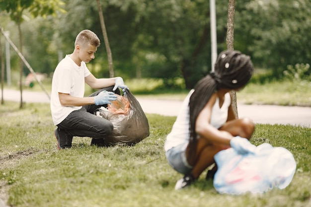 Afrikanisches mädchen und europäischer junge pivcking müll. aktivisten räumen den park seitlich.
