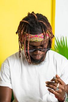 Afrikanisches männliches model mit tattoo rauchender zigarre