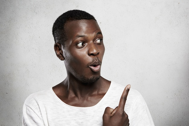 Afrikanisches männliches modell im weißen t-shirt, das mit schockiertem ausdruck an leerer wand schaut und finger auf kopierraum für ihren werbeinhalt zeigt.