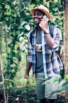 Afrikanisches mannreisendlächeln und entspannen sich im dschungel
