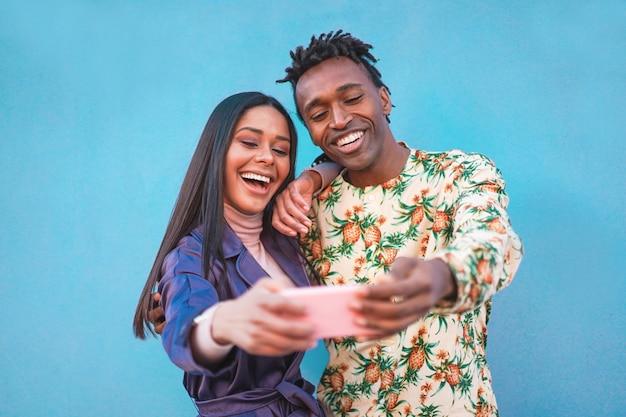 Afrikanisches paar, das selfie-foto für soziale netzwerkgeschichte nimmt. influencer menschen, die spaß mit neuer trendtechnologie haben