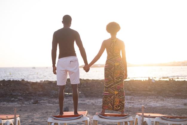 Afrikanisches paar der schwarzen rasse, das den warmen und goldenen sonnenuntergang über dem strand genießt, der auf den sonnenliegen steht und sich die hände nimmt. liebes- und beziehungskonzept für junge ethnische menschen
