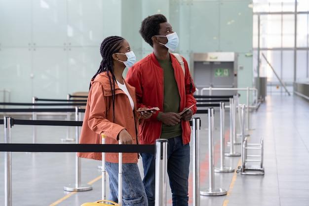 Afrikanisches paar mit gesichtsmasken, das auf das einsteigen in das flugzeug am flughafen wartet waiting