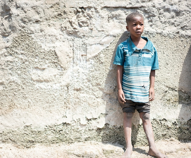 Afrikanisches schwarzes jungenporträt, das allein in der nähe seines armenhauses steht