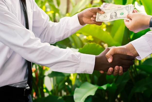 Afrikanisches und asiatisches geschäftsmannhändeschütteln mit geld selektiver fokus.