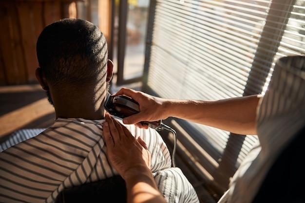 Afro-amerikaner, der sich im friseursalon die haare schneiden lässt