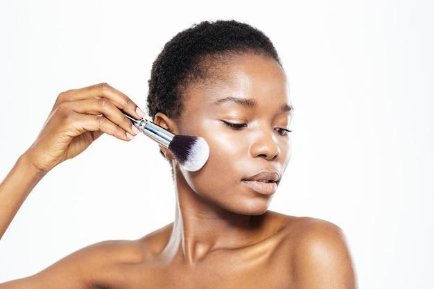 Afro-amerikanerin beim schminken mit pinsel auf weißem hintergrund