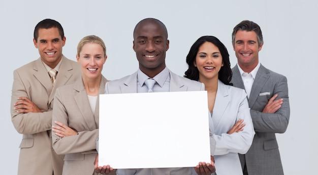 Afro-amerikanischer geschäftsmann, der eine weiße karte mit seinem team hält