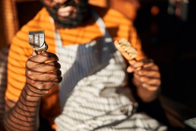 Afro-amerikanischer mann mit vintage-haarschneider und bürste