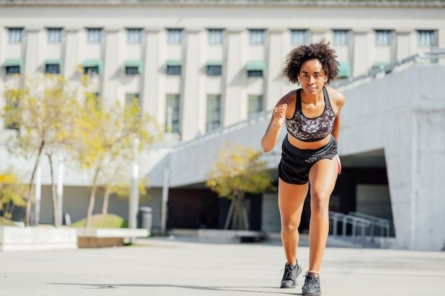 Afro athletische frau, die draußen auf der straße läuft und übung macht. sport und gesunder lebensstil.