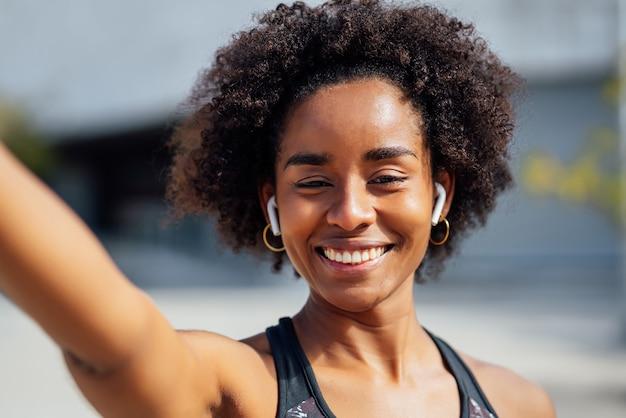 Afro athletische frau, die ein selfie nimmt, während sie draußen auf der straße steht. sport und gesunder lebensstil.