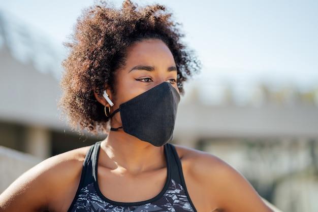 Afro athletische frau, die gesichtsmaske trägt und sich nach dem training draußen auf der straße entspannt. neuer normaler lebensstil. sport und gesunder lebensstil.
