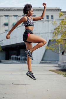 Afro athletische frau, die übung draußen auf der straße tut. sport und gesunder lebensstil konzept.