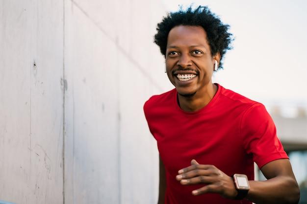 Afro athletischer mann macht sport und läuft im freien treppen hoch