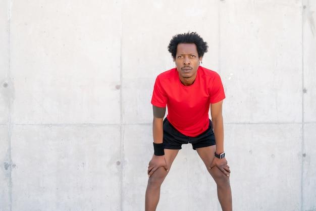 Afro athletischer mann ruht sich nach dem training im freien aus. sport und gesundes lifestyle-konzept.