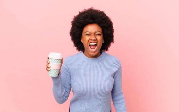 Afro-frau, die aggressiv schreit, sehr wütend, frustriert, empört oder verärgert aussieht, nein schreit. kaffeekonzept