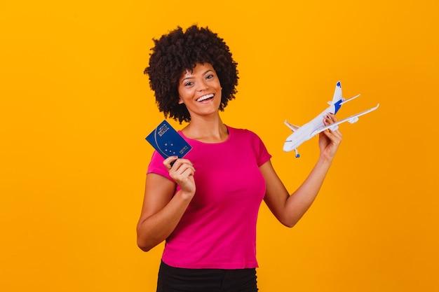 Afro-frau, die ein spielzeugflugzeug und einen brasilianischen pass hält. reisekonzeptafro-frau, die ein spielzeugflugzeug und einen brasilianischen pass hält. reisekonzept