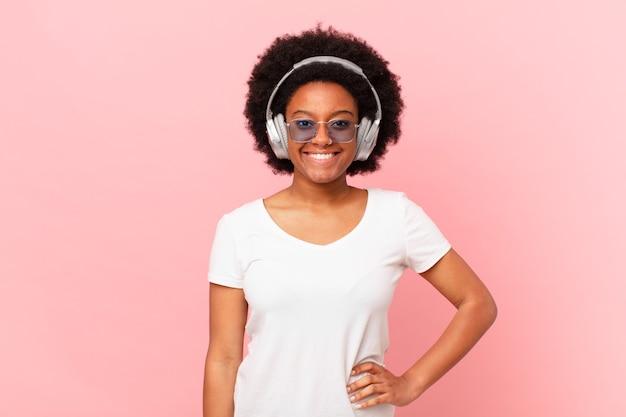 Afro-frau, die glücklich mit einer hand auf der hüfte und selbstbewusster, positiver, stolzer und freundlicher haltung lächelt. musikkonzept