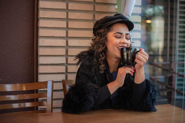 Afro-frau, die im winter kaffee oder heiße schokolade in der bäckerei trinkt.