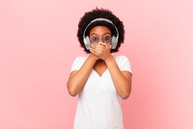 Afro-frau, die mit einem schockierten, überraschten ausdruck den mund mit den händen bedeckt, ein geheimnis hält oder oops sagt. musikkonzept