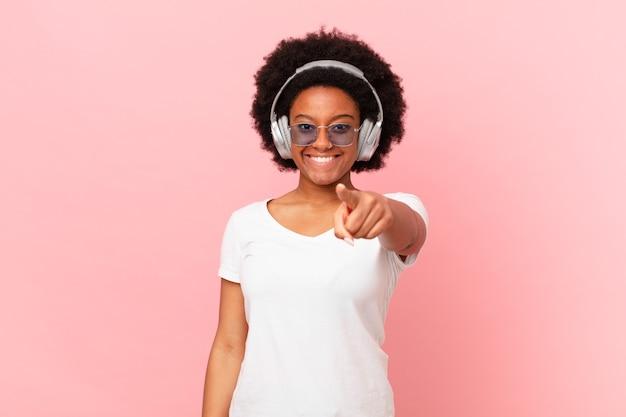 Afro-frau, die mit einem zufriedenen, selbstbewussten, freundlichen lächeln auf die kamera zeigt und sie wählt. musikkonzept