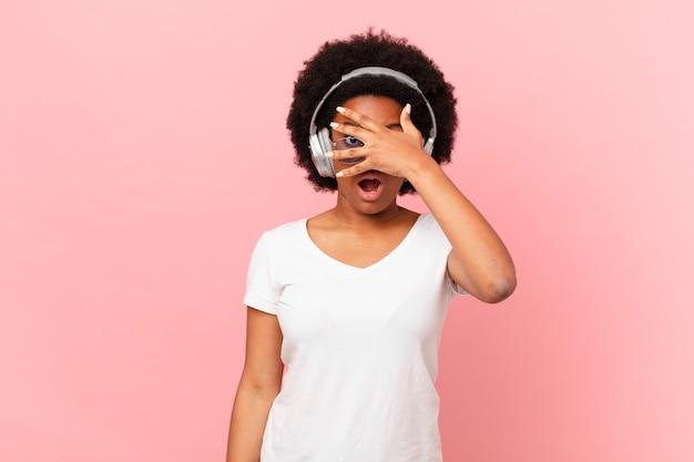 Afro-frau, die schockiert, verängstigt oder verängstigt aussieht, das gesicht mit der hand bedeckt und zwischen den fingern späht.
