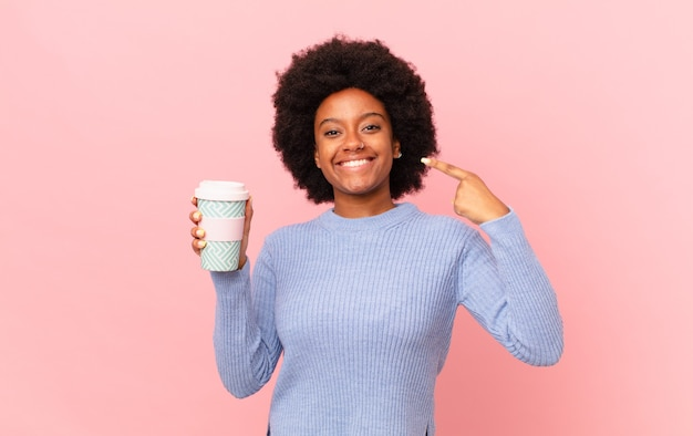 Afro-frau, die selbstbewusst lächelt und auf ihr eigenes breites lächeln, positive, entspannte, zufriedene haltung zeigt. kaffeekonzept