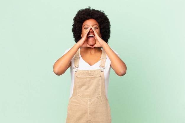Afro-frau, die sich glücklich, aufgeregt und positiv fühlt, mit den händen neben dem mund einen großen schrei ausspricht und das kochkonzept ausruft