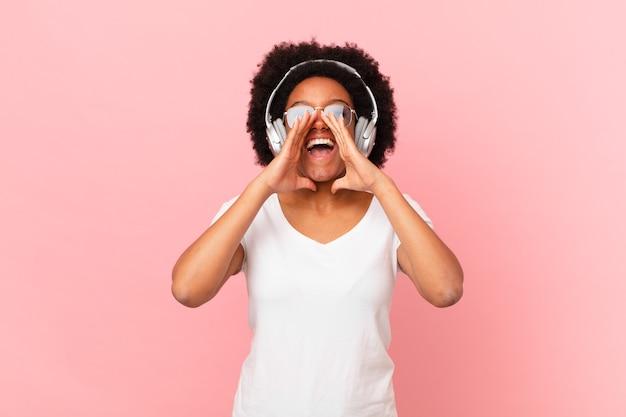 Afro-frau, die sich glücklich, aufgeregt und positiv fühlt, mit den händen neben dem mund einen großen schrei ausspricht und ruft. musikkonzept
