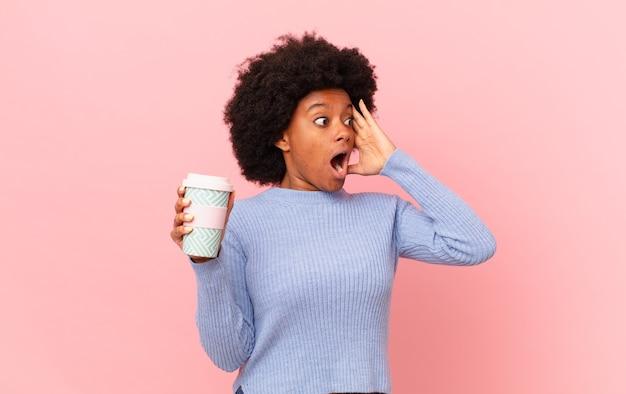 Afro-frau, die sich glücklich, aufgeregt und überrascht fühlt und mit beiden händen im gesicht zur seite schaut. kaffeekonzept