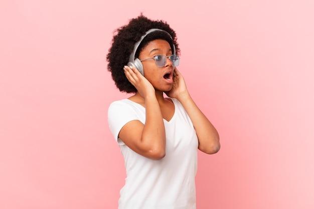 Afro-frau, die sich glücklich, aufgeregt und überrascht fühlt und mit beiden händen im gesicht zur seite schaut. musikkonzept