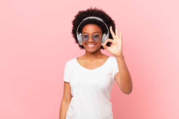 Afro-frau, die sich glücklich, entspannt und zufrieden fühlt, zustimmung mit okayer geste zeigt und lächelt. musikkonzept