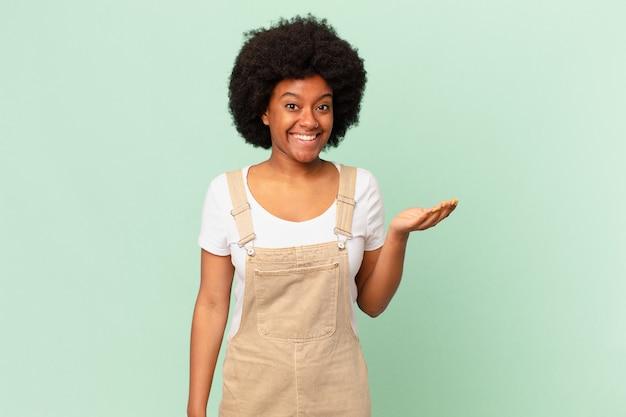 Afro-frau, die sich glücklich, überrascht und fröhlich fühlt, mit positiver einstellung lächelt und eine lösung oder ein ideenkochkonzept realisiert