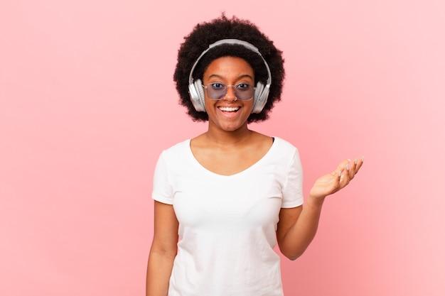 Afro-frau, die sich glücklich, überrascht und fröhlich fühlt, mit positiver einstellung lächelt und eine lösung oder idee realisiert. musikkonzept