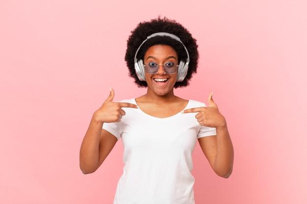 Afro-frau, die sich glücklich, überrascht und stolz fühlt und mit einem aufgeregten, erstaunten blick auf sich selbst zeigt. musik