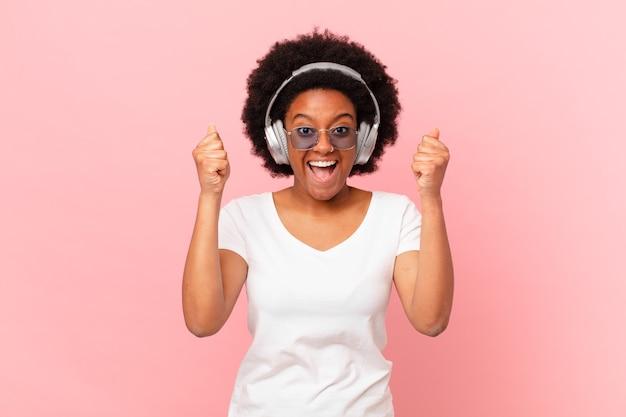 Afro-frau, die sich schockiert, aufgeregt und glücklich fühlt, lacht und erfolge feiert und sagt wow!