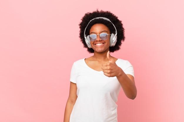 Afro-frau, die sich stolz, sorglos, selbstbewusst und glücklich fühlt und positiv mit daumen nach oben lächelt. musikkonzept
