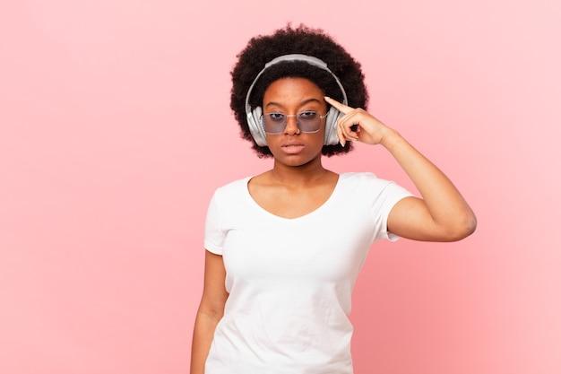 Afro-frau, die sich verwirrt und verwirrt fühlt und zeigt, dass sie verrückt, verrückt oder verrückt sind. musikkonzept