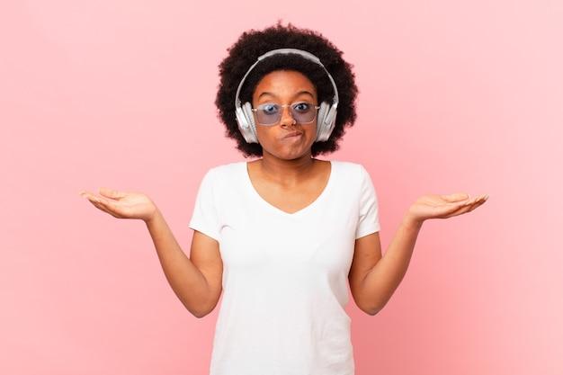 Afro-frau, die sich verwirrt und verwirrt fühlt, zweifelt, gewichtet oder verschiedene optionen mit lustigem ausdruck wählt. musikkonzept