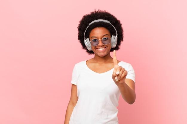 Afro-frau, die stolz und selbstbewusst lächelt und die nummer eins triumphierend posiert und sich wie ein anführer fühlt. musikkonzept