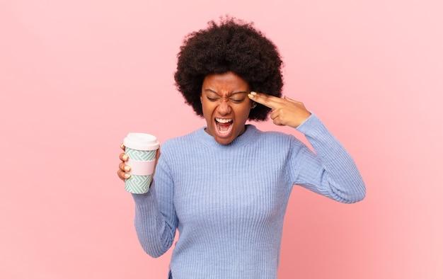 Afro-frau, die unglücklich und gestresst aussieht, selbstmordgeste, die waffenzeichen mit der hand macht und auf den kopf zeigt. kaffeekonzept