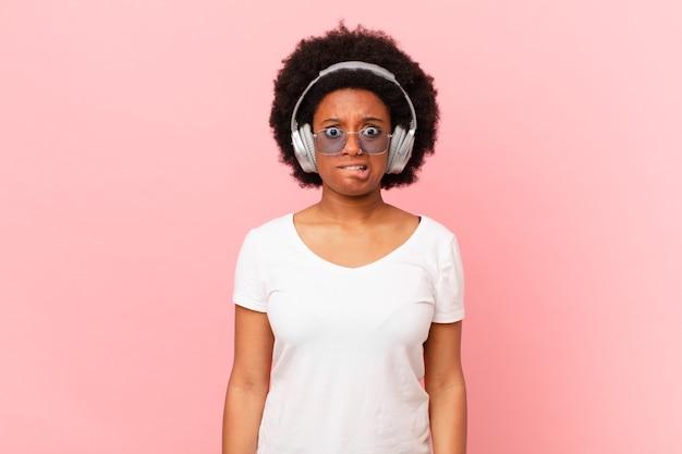 Afro-frau, die verwirrt und verwirrt aussieht, sich mit einer nervösen geste auf die lippe beißt und die antwort auf das problem nicht kennt. musikkonzept