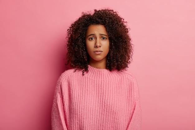 Afro frau hat bedauernden blick, unzufriedenen gesichtsausdruck, gekleidet in freizeitkleidung, unglücklich mit schlechten nachrichten, schaut traurig in die kamera, trägt pullover, isoliert auf rosa hintergrund.