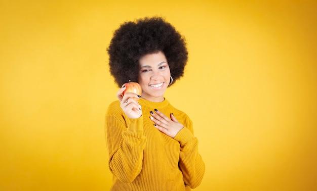Afro-frau lächelt mit einem apfel in den händen auf gelbem hintergrund smiling